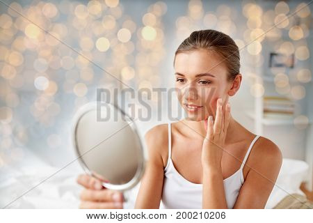people and beauty concept - beautiful woman with mirror sitting on bed at home bedroom and touching her face skin