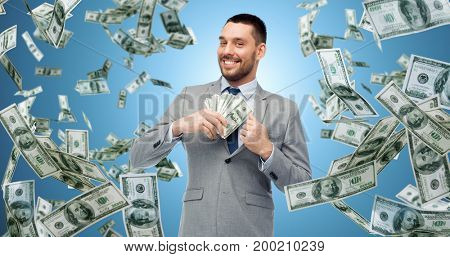 business, people and finances concept - smiling businessman with bundle of american dollar cash money over blue background
