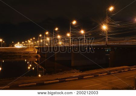 Bridge over the river with yellow lanterns at night highway