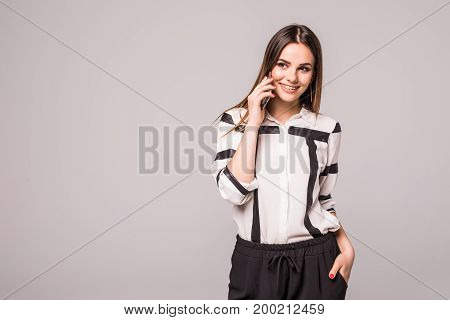 Portrait Of A Laughing Attractive Young Woman Talk On A Mobile Phone Laughing At The Camera Over Gre