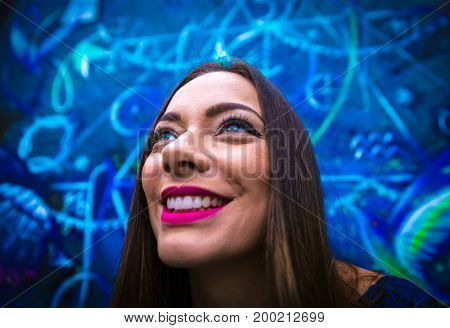 Pretty brunette woman against painted wall