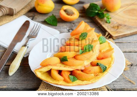 Omelette or omelet with apricot filling. Fried eggs omelette stuffed with fresh apricot slices and mint on a white serving plate. Fork, knife, napkins on a vintage wooden table. Closeup
