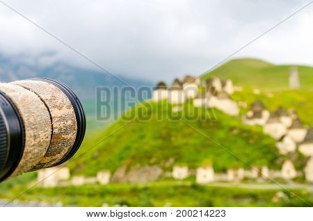 Close up lense of professional camera taking picture of crypts of City of the Dead in republic of North Ossetia, Russia