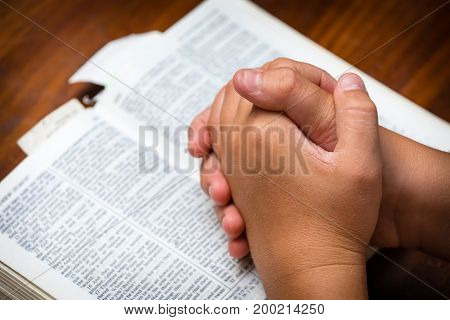 A young teenager praying over the bible in black and white