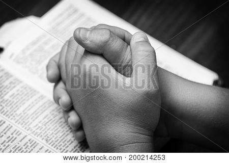 A young boy praying over the bible in black and white