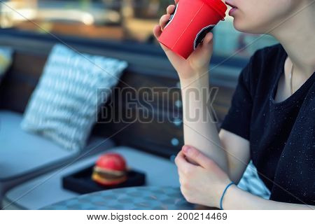 Closeup image of young woman in outdoors restaurant drinking coffee from red paper cup with burger in front of her