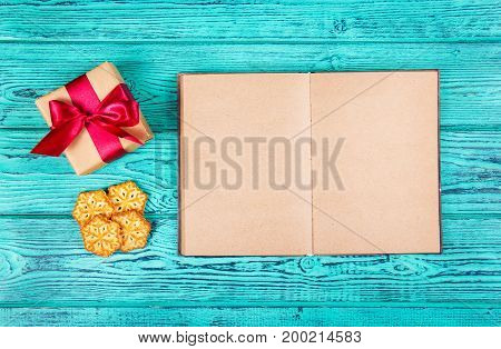 An open book with blank pages a gift box with a bow and Christmas cookies. Cookies in the form of snowflakes and a Christmas gift. Copy space