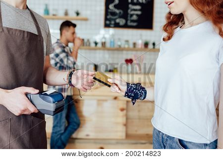 young woman giving credit card to waiter holding payment terminal in cafe
