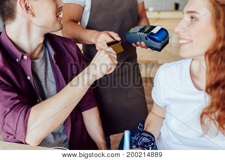 Couple Paying By Credit Card In Cafe