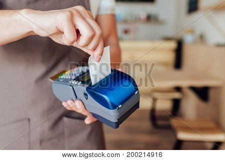 cropped shot of waiter receiving payment with credit card and terminal