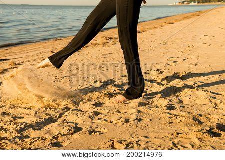 Closeup image of woman's legs in black trousers on seashore