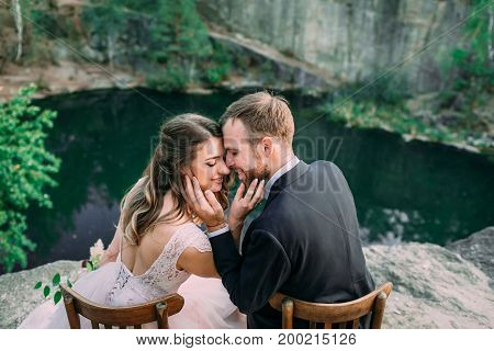 Newlyweds Sitting At The Edge Of The Canyon And Couple Looking Each Other With Tenderness And Love.