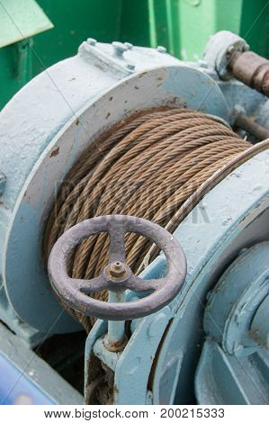 Winch with rope and rusty crane on a ship on the river