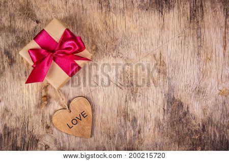 Present for the day of lovers. Gift box and wooden heart. St. Valentine's Day. Romantic concept.