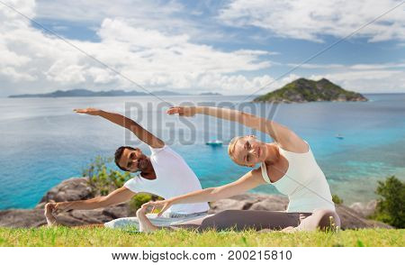 fitness, sport, people and recreation concept - smiling couple making yoga exercises sitting on mats outdoors over ocean background