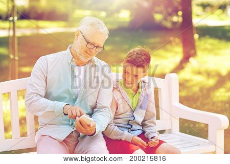 family, generation, technology and people concept - happy grandfather and grandson with smartphones at summer park