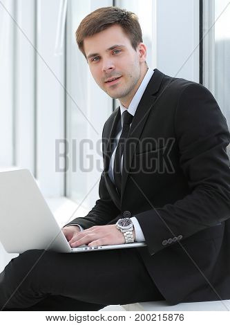 young professional with laptop on background of office window