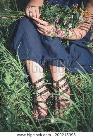 Woman Legs Sitting In Grass On Summer Meadow