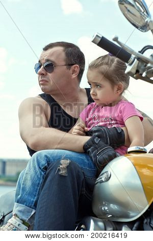 Girl with dad sitting on the bike and looking into the distance.
