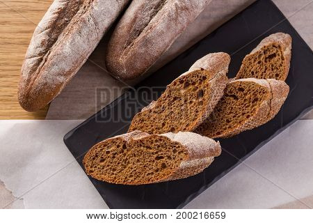 French homemade baguette bread. Rye baguette on black shale. cut baguette on the wooden table.