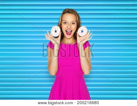 people, sweets and fast food concept - happy young woman or teen girl in pink dress with donuts over blue ribbed background