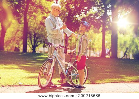 family, generation, safety and people concept - happy grandfather and boy with bicycle and bike helmet at summer park