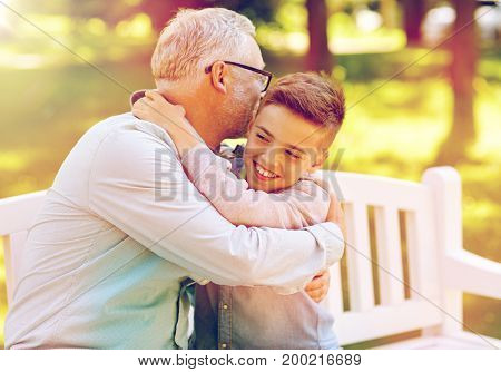 family, generation, relations and people concept - happy grandfather and grandson hugging on bench at summer park