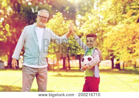 family, generation, gesture, sport and people concept - happy grandfather and grandson with football ball making high five at at summer park