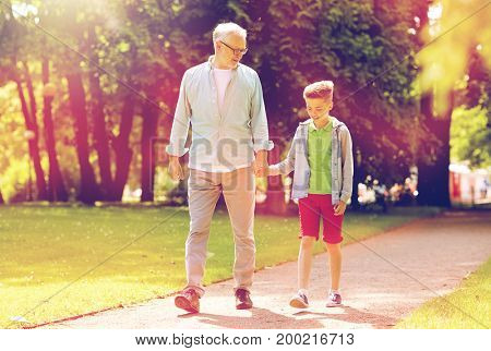 family, generation, communication and people concept - happy grandfather and grandson walking at summer park