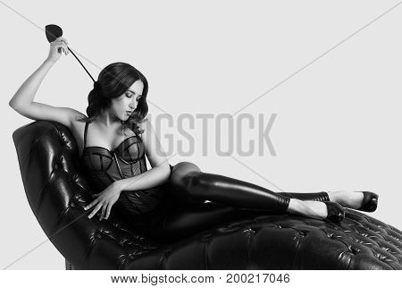 Sexy elegant woman lies in a corset on a leather sofa. Sensual woman posing on couch. Monochrome. Copy space