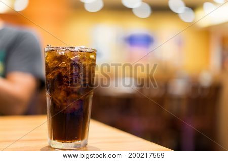 Cool ice soft drink cola carbonated liquid fresh food with soda water white dish on wooden table with handsome man sitting brown sofa in pizzeria restaurant.