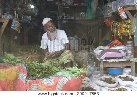 Dhaka, bangladesh, august 2017- A old religious man wearing traditional mulim dress thiking deeply and also selling grocery product at his own shop near street , taken on August 17, 2017 at Motijhil, Dhaka, Bangladesh.