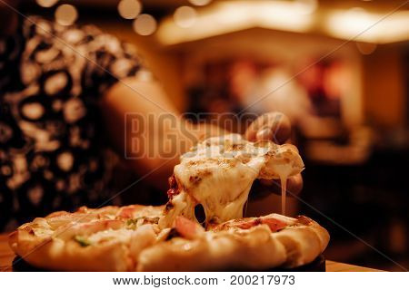 Slice of hot pizza cheese lunch or dinner crust seafood meat topping sauce. with bell pepper vegetables delicious tasty fast food italian traditional on wooden board table classic in side view .