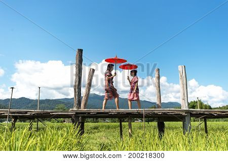 The Women holding a red umbrella and walk on the wooden bridge in the green rice field. Mae Hongson Thailand. Travel Concept