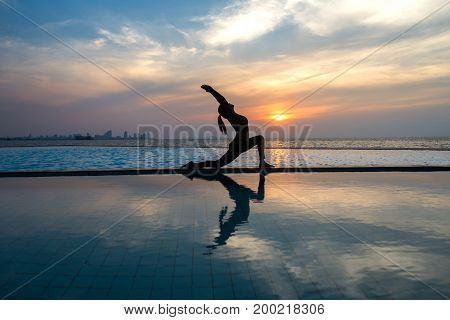 Silhouette young woman practicing yoga on swimming pool and the beach at sunset. Healthy Concept.