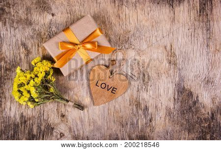A box with a gold ribbon on an old wooden background. Wooden heart and flowers. Copy space. Flat lay