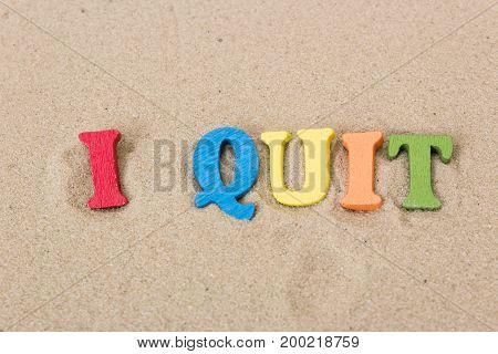 Word I Quit of colored wooden letters on sandy beach