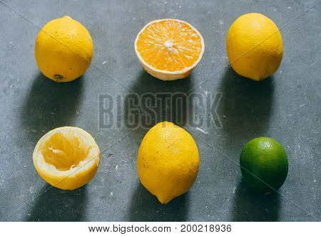 An arrangement of citrus fruits lemons orange and limes on a gray background.