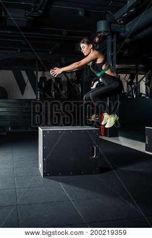 Young woman doing a box jump exercise. Muscular woman doing a box squat at the gym