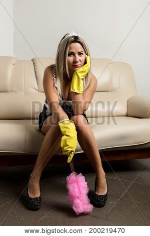 young attractive woman or housewife sitting on a masters couch with rubber washing gloves, bored and tired in stress of domestic housework concept.