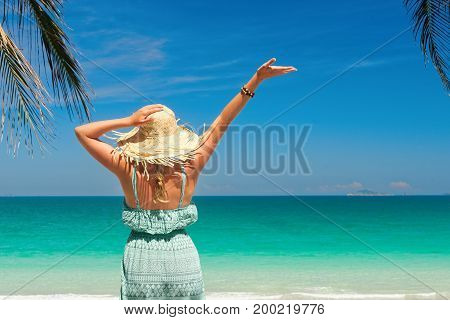 joyful woman with arm up on beach is enjoying serene ocean nature in summer during holidays travel. Travel to Asia happiness emotion summer holiday concept.
