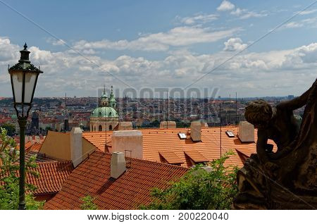Bird's eye view of Prague panorama. Red roofs and lantern in the foreground.