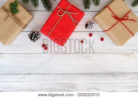 Chrismas and new year background - fir leaves with decorations and handmade gift boxs on white wooden backgrond. Flat lay top view