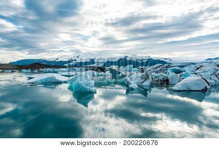 Glacial lagoon in Iceland, cloudy weather, mountains on the horizon. The glacial lake reflects the sky.