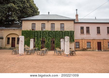 SYDNEY,NSW,AUSTRALIA-NOVEMBER 19,2016: Hyde Park Barracks Museum historic compound courtyard with outdoor seating and climbing ivy on a cloudy day in Sydney, Australia.