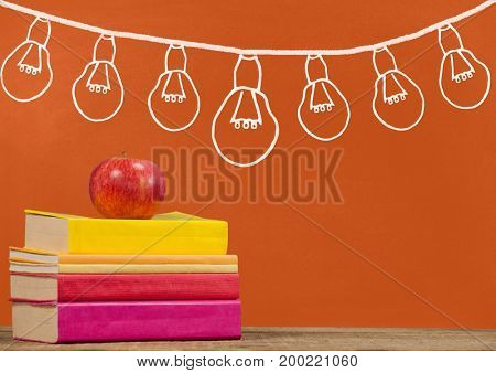 Digital composite of Books on the table against orange blackboard with graphics