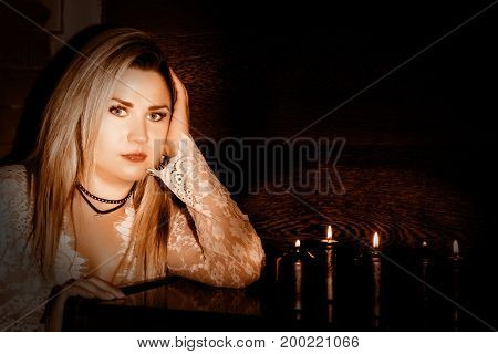 Young woman in white transparent dress stending near black candels, Divination and black magic concept.