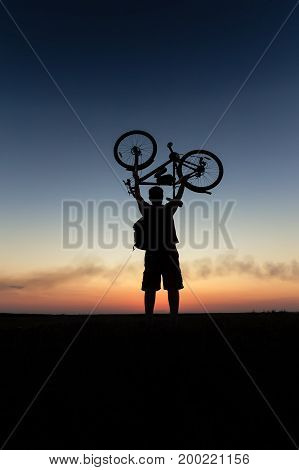 silhouette with the bike / the man with the bike in the hands of the sunset