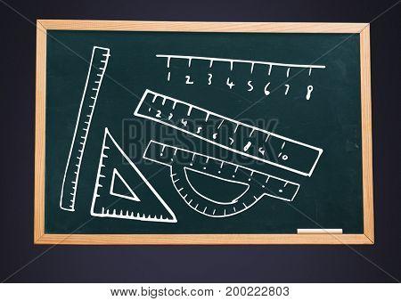 Digital composite of rulers on blackboard