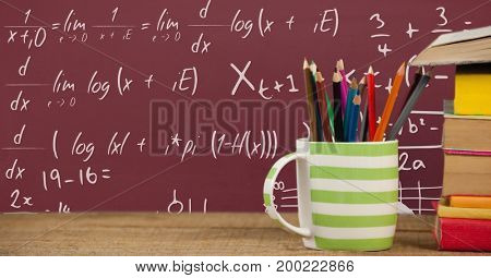 Digital composite of Books on the table against red blackboard with education and school graphics